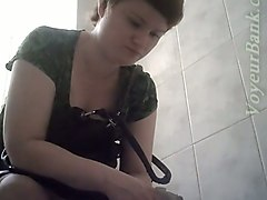brunette chubby white lady in green dress filmed in the toilet