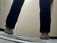 white lady in blue jeans filmed from behind in the toilet